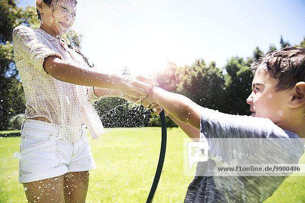 Bruder und Schwester spritzen Wasser mit Gartenschlauch