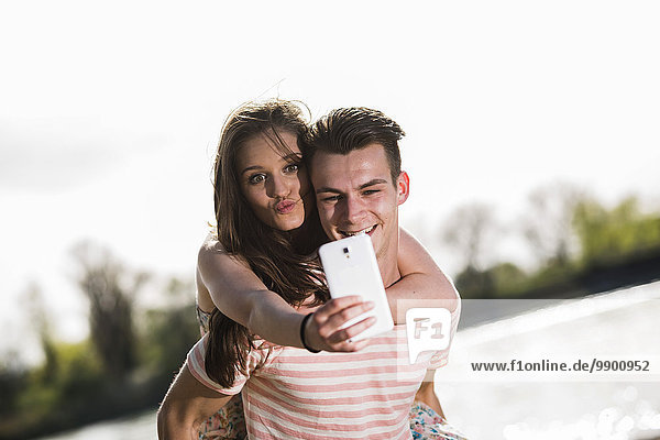 Verspieltes junges Paar mit Selfie im Freien