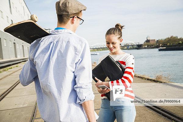 Junger Mann und Frau  die am Flussufer reden.