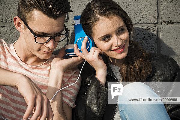 Lächelndes junges Paar mit Kopfhörern