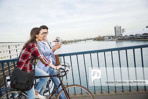 Deutschland  Mannheim  junger Mann und Frau mit Fahrrad und Handy auf Brücke