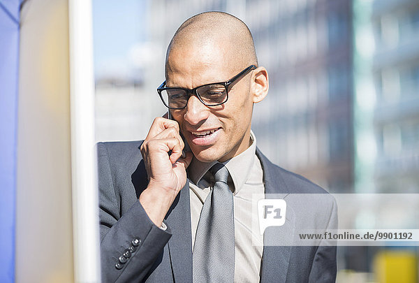 Businessman outdoors on cell phone