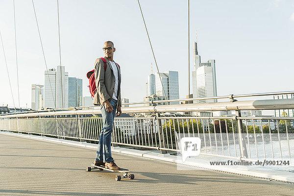 Deutschland  Frankfurt  Mann Skateboarding auf der Brücke