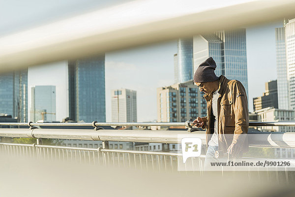 Deutschland  Frankfurt  Mann auf Brücke mit Skateboard sucht auf Smartphone