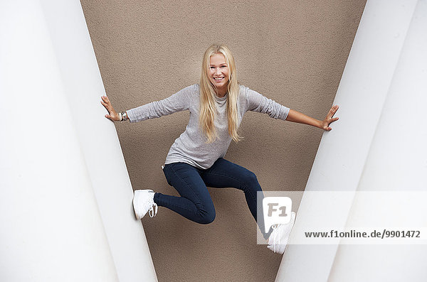 Porträt einer lächelnden blonden Teenagerin zwischen Betonsäulen