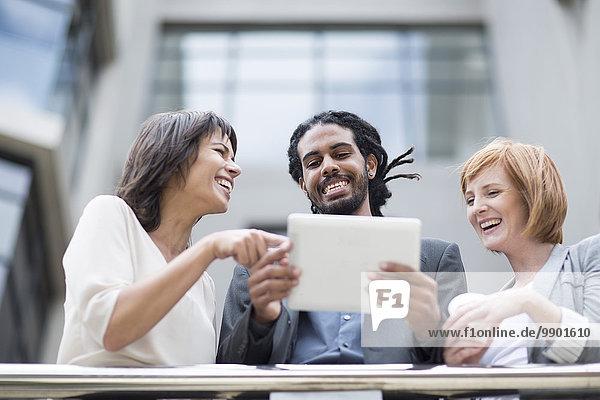 Geschäftsleute  die auf dem Balkon stehen und ein digitales Tablett benutzen.