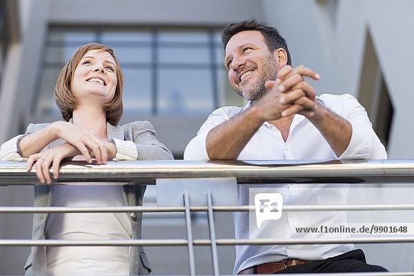 Geschäftsleute in der Pause  auf dem Balkon stehend
