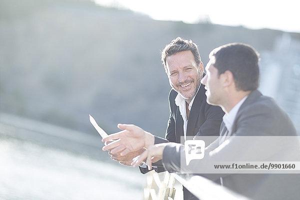 Geschäftsleute  die sich am Geländer lehnen und reden