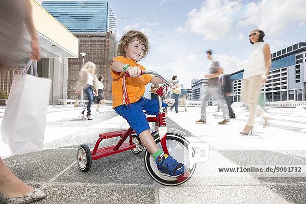Ein Junge auf einem Dreirad zwischen einer Menschenmenge in einer Stadt.