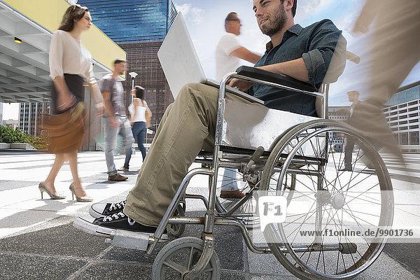 Ein Mann im Rollstuhl arbeitet an seinem Laptop zwischen einer Menschenmenge in einer Stadt.