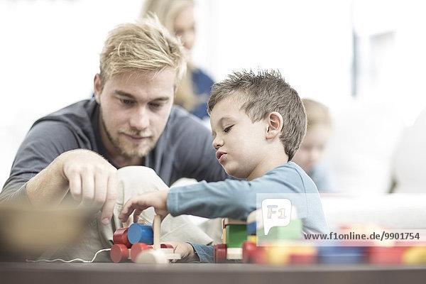 Vater und kleiner Sohn spielen mit Holzspielzeug