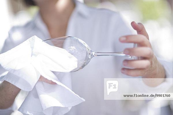Kellnerin beim Reinigen eines Weinglases mit einem Tuch
