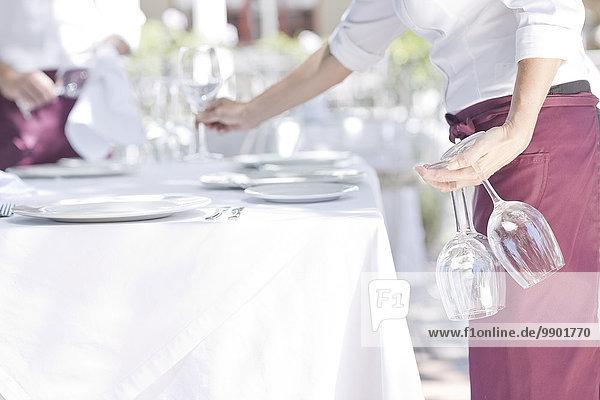 Kellner stellt Weingläser auf den Tisch des Restaurants im Freien.