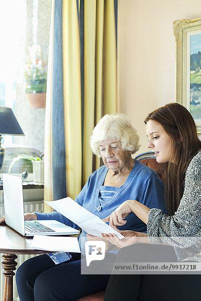 Großmutter und Enkelin lesen das Dokument  während sie zu Hause den Laptop benutzen.