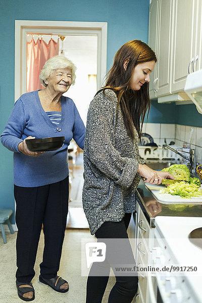Fröhliche ältere Frau mit Enkelin bei der Zubereitung des Essens in der Küche zu Hause