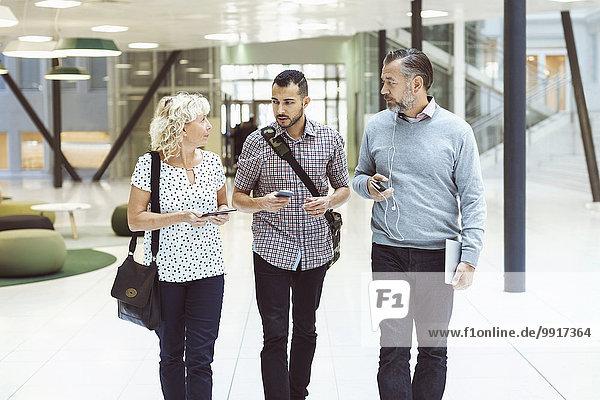 Geschäftsleute mit Technologien diskutieren in der modernen Bürolobby