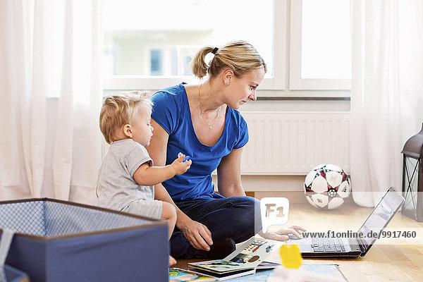 Baby Junge mit Mutter mit Laptop zu Hause