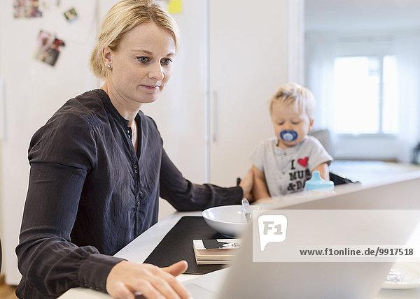Frau arbeitet am Laptop  während sie sich um den kleinen Jungen am Esstisch kümmert.