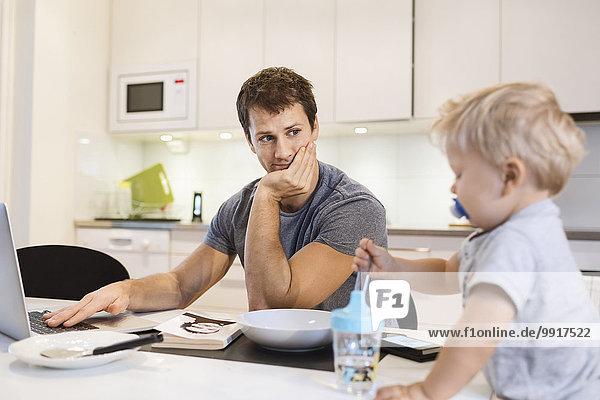Vater schaut auf den kleinen Jungen  während er den Laptop in der Küche benutzt.