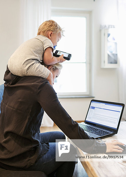 Mother using laptop while carrying baby boy on shoulders at home