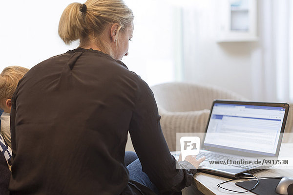 Rückansicht der Frau mit Laptop von Baby Boy zu Hause