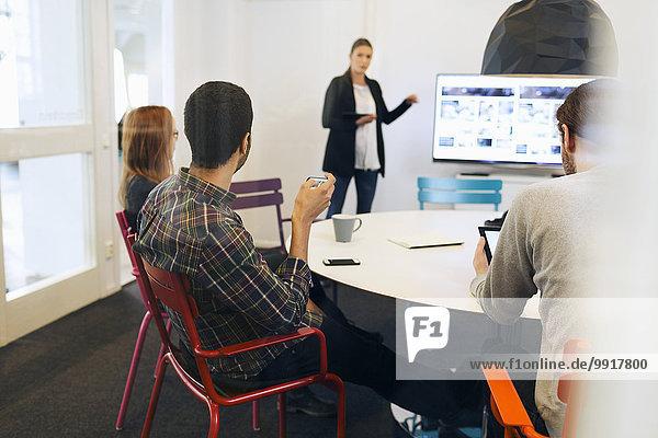 Geschäftsfrau erklärt während der Telefonkonferenz im Vorstandszimmer des Kreativbüros