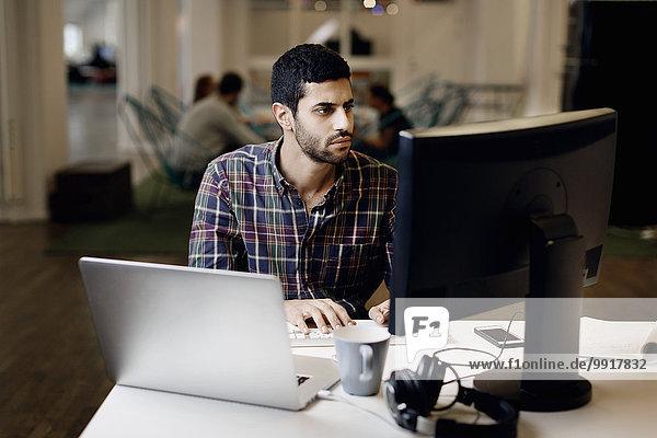 Geschäftsmann arbeitet spät am Desktop-PC im Kreativbüro