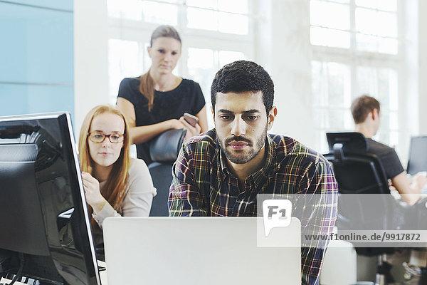 Geschäftsfrauen  die einen männlichen Kollegen mit Laptop am Schreibtisch im Kreativbüro anschauen