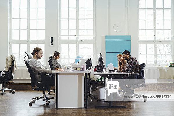 Geschäftsleute  die an Schreibtischen arbeiten  um Arbeitsplätze zu schaffen.