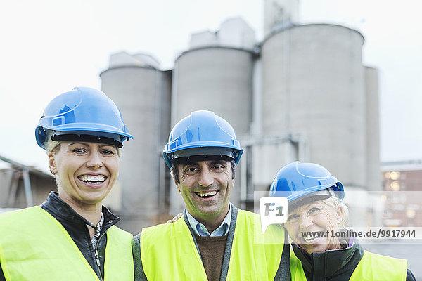 Porträt von selbstbewussten Arbeitern mit Schutzhelmen in der Fabrik