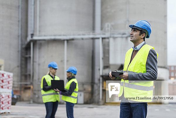 Männlicher Arbeiter  der ein digitales Tablett benutzt  während er in die Fabrik schaut.