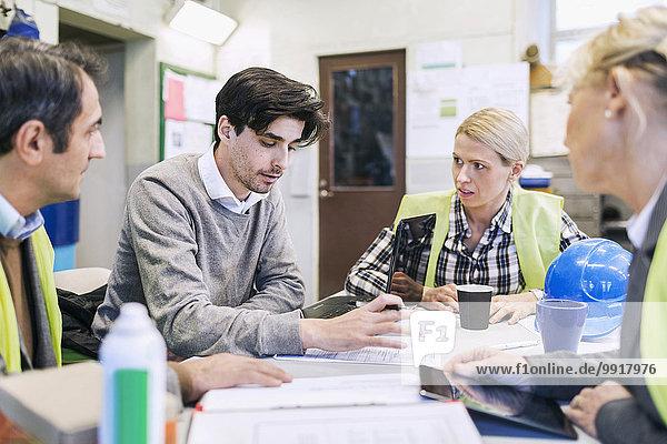 Junger männlicher Arbeiter im Gespräch mit Kollegen am Tisch in der Fabrik