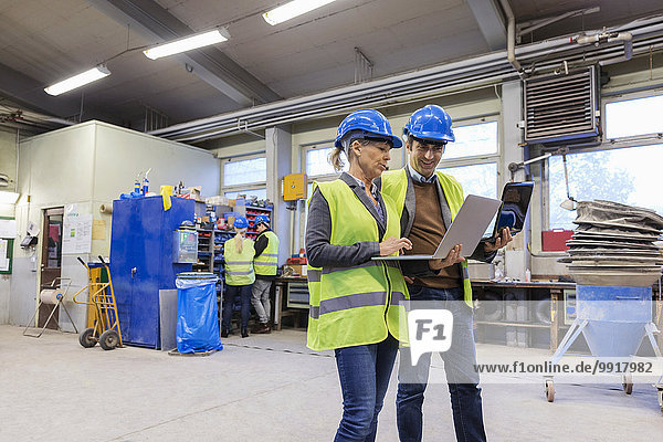 Arbeiterinnen und Arbeiter  die Laptops in der Fabrik benutzen