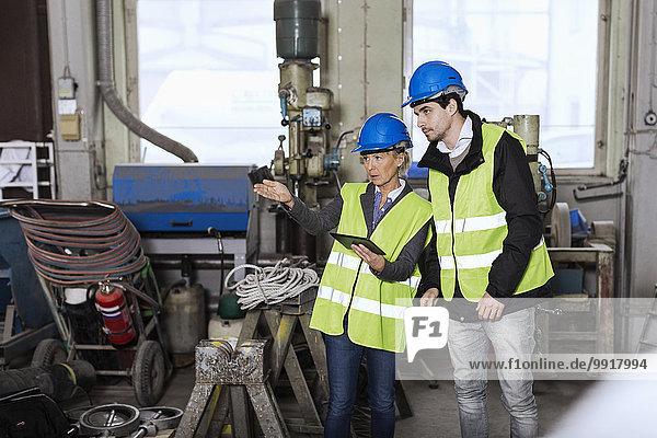 Handwerker mit digitalem Tablett diskutieren in der Fabrik