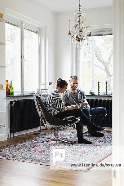 Volle Länge der Paar-Shopping durch digitale Tablette und Kreditkarte zu Hause