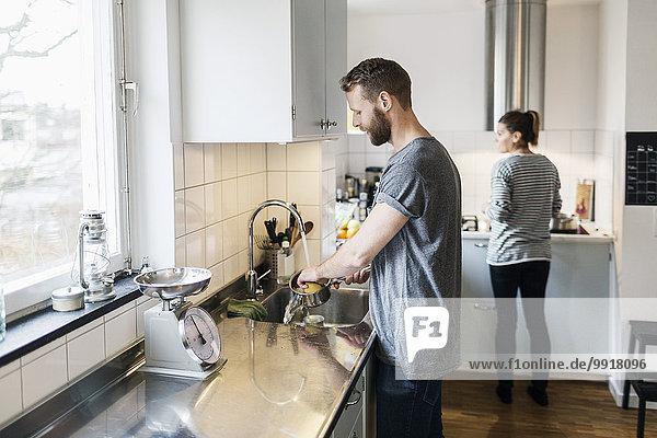 Mann wäscht Soßenpfanne  während Frau im Hintergrund in der Küche steht.