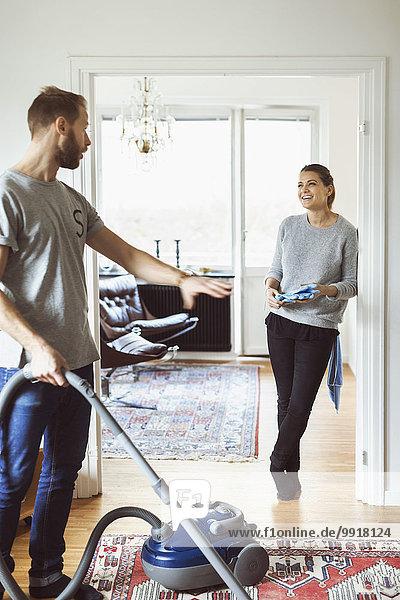 Mann mit Staubsauger im Gespräch mit der Frau zu Hause