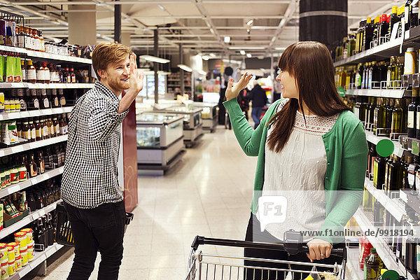 Mann und Frau winken sich im Supermarkt zu.