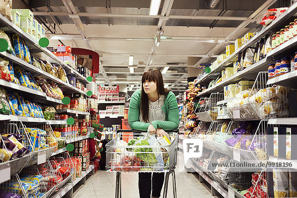 Junge Frau stützt sich auf Einkaufswagen am Supermarktgang