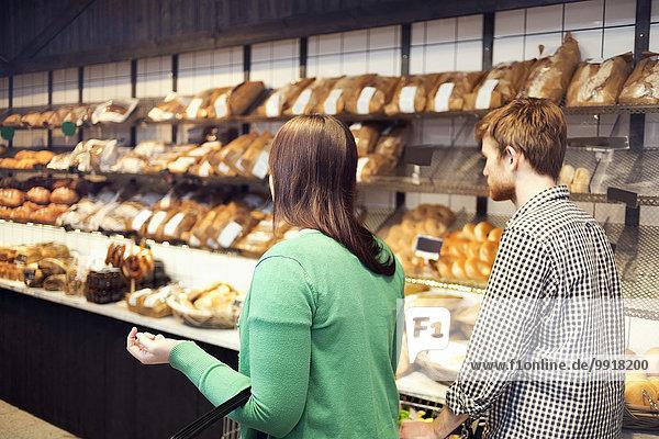 Junges Paar beim Broteinkauf im Supermarkt