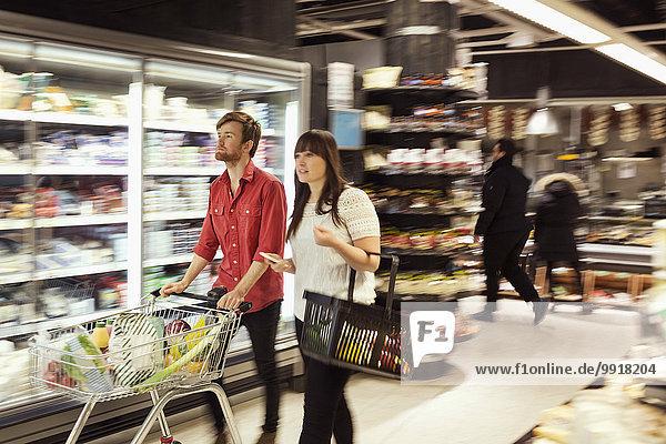 Junges Paar mit Lebensmittelgeschäften im Supermarkt