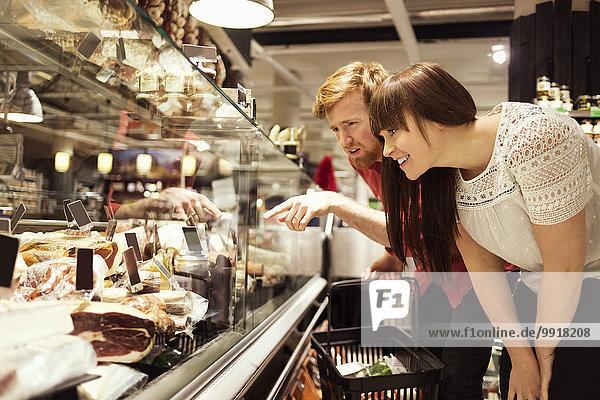 Junges Paar wählt Frischfleisch im Supermarkt