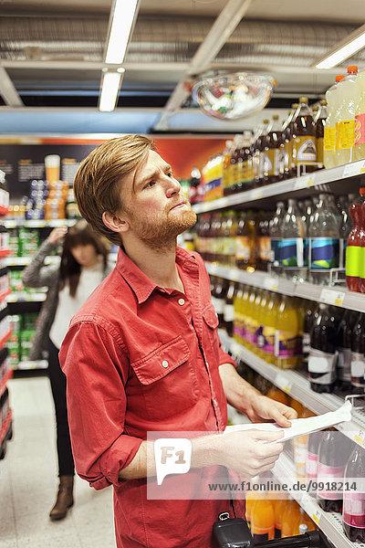 Mann mit Liste beim Einkaufen im Supermarkt