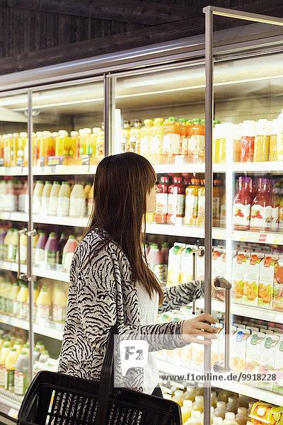 Frau beim Einkaufen in der Tiefkühltruhe im Supermarkt