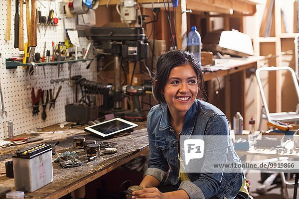 Porträt einer Mechanikerin in der Werkstatt  wegblickend  lächelnd