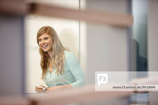 Geschäftsfrau präsentiert am Whiteboard im Büro