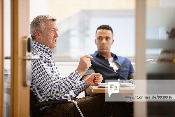 Businessmen having team meeting in conference room