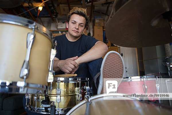 Portrait eines jungen männlichen Schlagzeugers im Keller