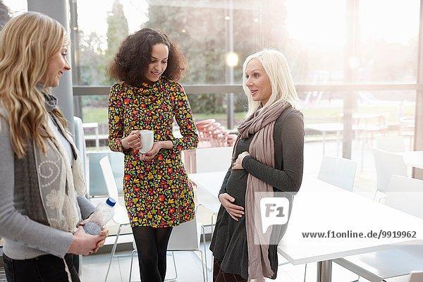 Schwangere Geschäftsfrau im Gespräch mit Kolleginnen im Büro