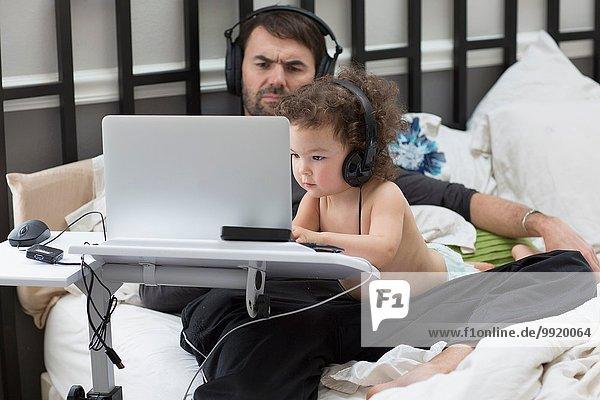 Vater beobachtet Kleinkind Tochter Tippen auf Laptop im Bett